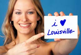 Photo of woman with card that reads I Love Louisville