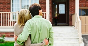 Photo of a couple in front of their home