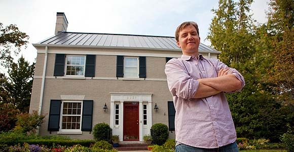 Photo of Dan Hofmann in front of a Louisville home with solar panels on the roof