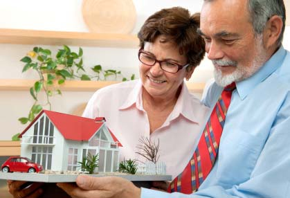 Photo of a senior couple looking at a model of their Louisville dream home