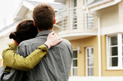 Photo of a young couple in front of a condo