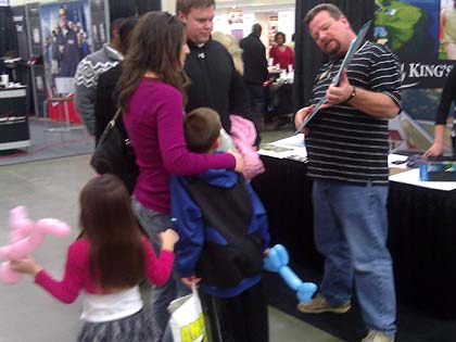 Photo of parents speaking with exhibitor while children play with their balloon animals