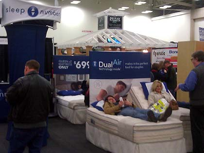 Photo of some people trying out the Sleep Number bed by Select Comfort