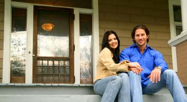 Photo of couple sitting on front porch in front of new front door