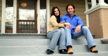 Photo of a young couple in front of their Louisville home