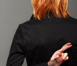 Photo of a woman with her fingers crossed behind her back.