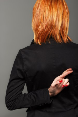 Photo of a woman with her fingers crossed behind her back. Top 7 Lies Realtors Tell
