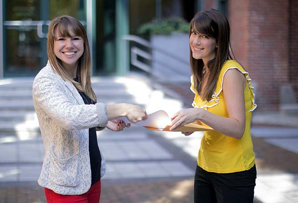 Photo of one woman smiling while another hands her a paper. Top 7 Lies Realtors Tell