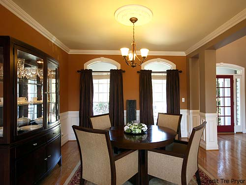 Photo of a formal dining room that's open to the family room and foyer.