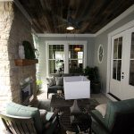 Photo of a covered porch with fireplace and concrete floors by Tre Pryor