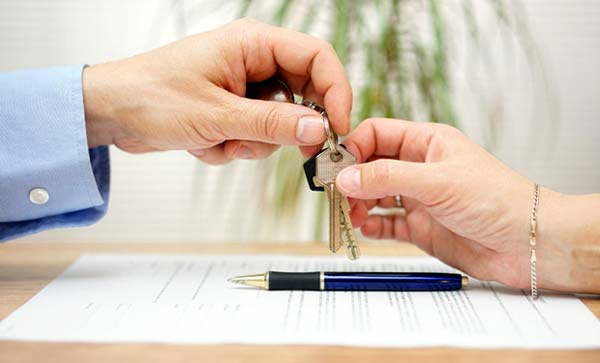 Photo of hands giving house keys