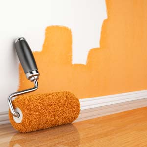 Photo of a paint roller and paint on the wall