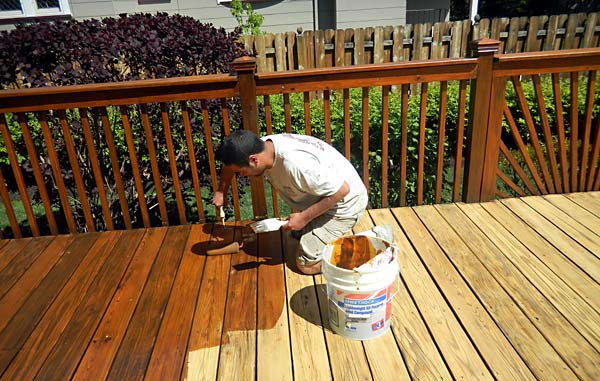 Photo of a man staining a wood deck