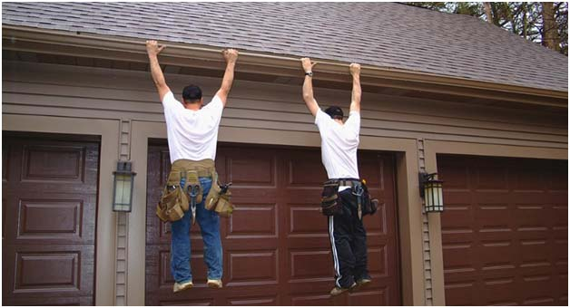 Photo of two men hanging on a home's gutters.