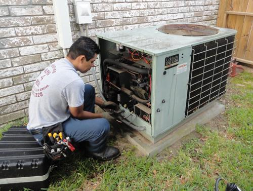 Photo of tech repairs an air conditioner