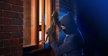 Image of criminal breaking into a home