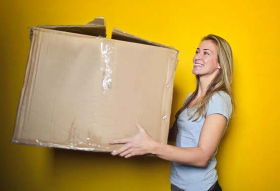 Photo of a woman carrying a moving box
