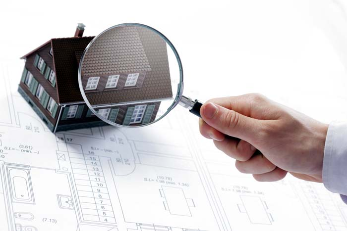 Photo of house under a magnifying glass - Seller's Guide to Home Inspections